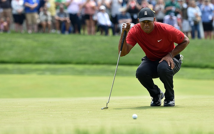 Tiger Woods makes sure he has the line on his birdie putt on No. 5.