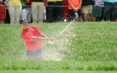 Tiger Woods chips out of a bunker on No. 13.