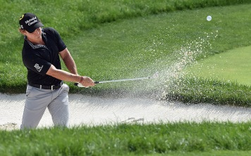 Bud Cauley chips out of the bunker on 17.