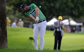 Marc Leishman hits his second shot from the rough on the way to a par at 17.