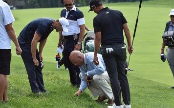 Martin Kaymer (left) and Adam Scott talk with PGA Rules Official Ken Tackett about Kaymer's plugged ball.